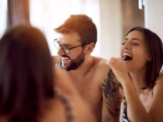 Happy men and women brushing their teeth in the bathroom