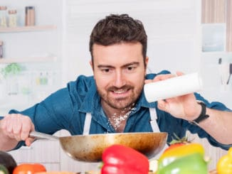 One man is cooking in his kitchen and adding salt