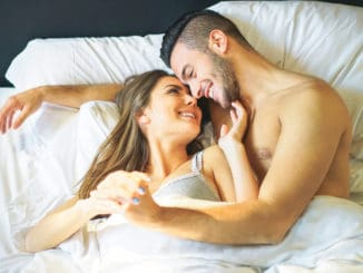 Young loving couple lying in bed cuddling looks each other under white blankets