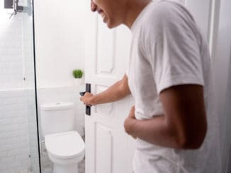 Man opening the toilet door and hold his stomach ache