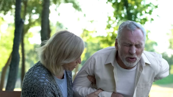 Senior man suffering sharp back pain, walking in park, caring wife helping him, stock photo
