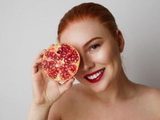Beauty woman with orange pomegranate cut in half over white background. Attractive fresh vitamin concept