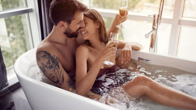 Beautiful young couple drinking champagne in the bathtub