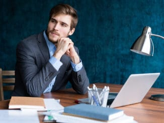 Shot of young man sitting at table looking away and thinking. Thoughtful businessman sitting in office