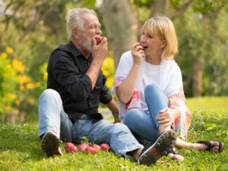 Happy senior couple relaxing in park eating apple together morning time.