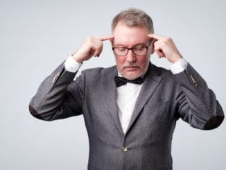 Senior man in suit and glasses holds fingers on temples, trying to remember or generate idea