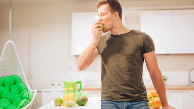 Young smiling handsome man bites organic green apple while cooking fresh fruits in the kitchen. Healthy eating. Vegetarian meal. Diet detox