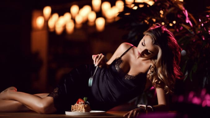 Young blonde woman eating strawberry cake desert in a cafe restaurant in the evening time celebrating birthday party