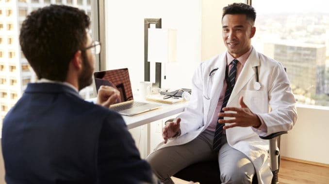 Man Having Consultation With Male Doctor In Hospital Office