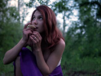 Young Beautiful Attractive woman in Purple Skirt in the forest with a hallucinogens mushroom at Mysterious Twilight.