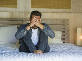 Lifestyle home portrait of young attractive stressed and depressed man sitting on bed worried and frustrated suffering depression crisis covering face with hands feeling desperate and helpless