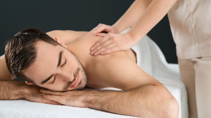 Handsome man receiving back massage on black background. Spa service