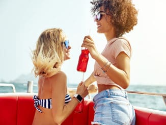 Two carefree young women having fun together while sitting on a boat on the ocean during their summer vacation