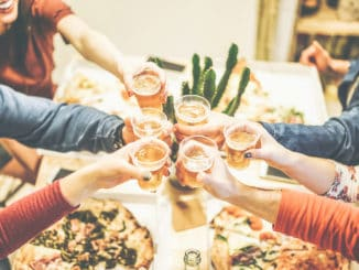 Group of friends enjoying dinner toasting with beers and eating take away pizza at home