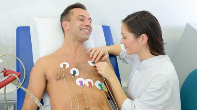 Nurse attaching heart monitor pads to patient cardio