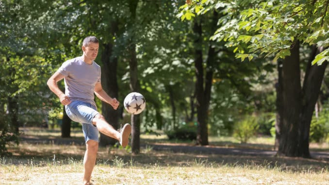 Handsome man playing football outdoors
