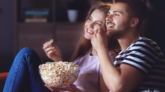 Young couple watching TV on sofa at night