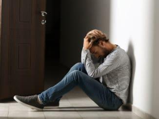 Depressed young man sitting on floor in dark corridor