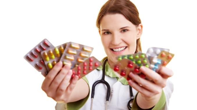 Smiling female doctor holding many colorful pills in her hands
