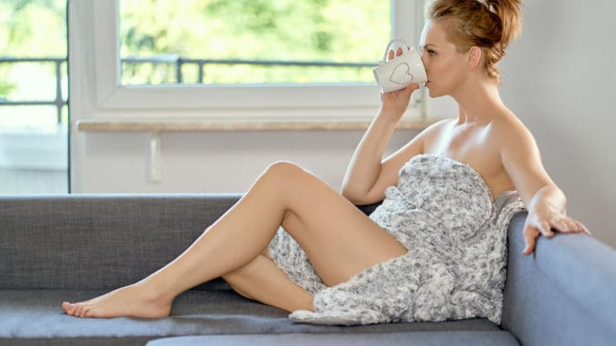 Attractive beautiful half naked woman drinking coffee on the sofa at home