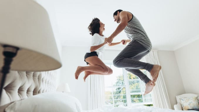 Man and women holding hands and jumping together on bed.