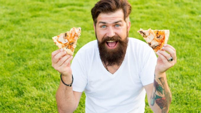 A lot of pizza. bearded men hipster eat pizza
