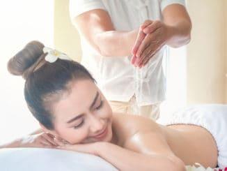 Asia beautiful women enjoying a salt scrub massage at the health spa in Thailand