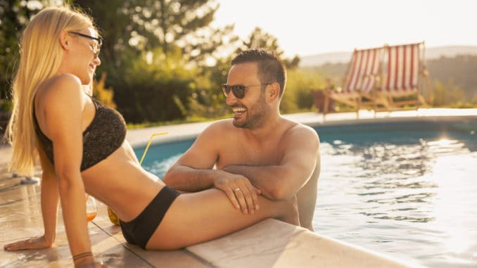 Couple in love at a poolside summer party, sitting at the edge of a swimming pool, sunbathing, drinking cocktails and having fun