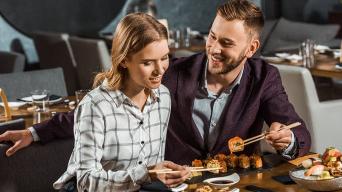 Attractive happy young adult couple eating sushi in restaurant