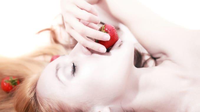 Portrait of beautifu lyingl woman with silver makeup eating strawberries closeup