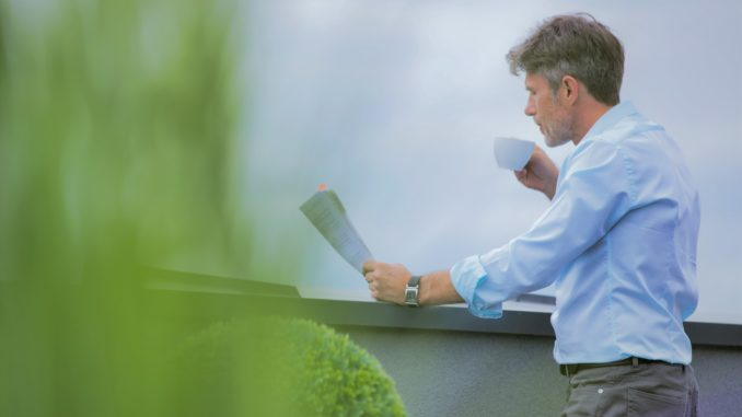 Senior business man reading his notes and enjoying a morning coffee whilst standing on his balcony