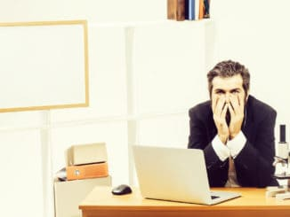 Tired young bearded man sitting at desk in front of computer with his chin resting on his hands at workplace