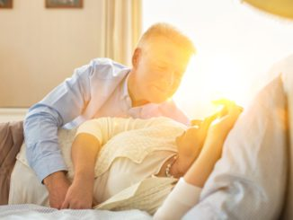 Sweet senior couple cuddling in bed with yellow lens flare in background