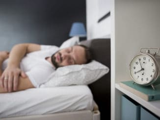 Man sleeping in his bedroom with alarm clock in foreground. It's morning