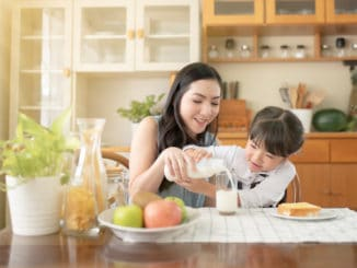 Asian mothers and daughters pour milk together. There is a bread with butter next to it for breakfast.