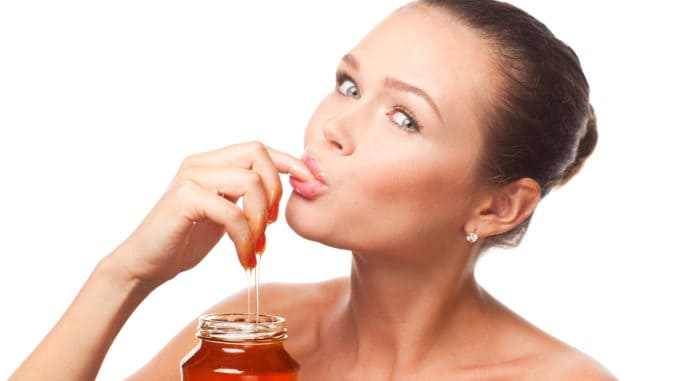 Attractive young adult with honey holding finger in the mouth isolated on white background