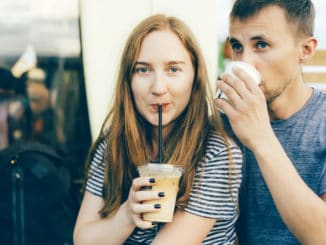 Close up portrait of a caucasian girl with a guy drinking coffee. Relations of modern millennials, coffeemania and urban style.