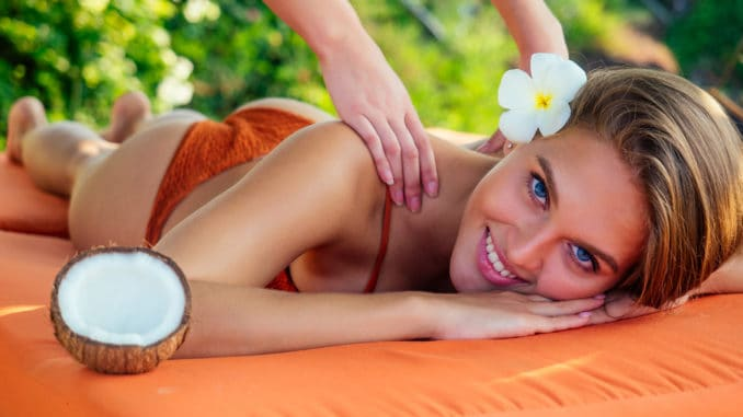 snow-white smile,perfect skin woman plumeria flower relaxing massage on beach.girl pampering in the Thai spa salon and coconut oil masseuse bliss tropical paradise.tourist traveling rich resort.