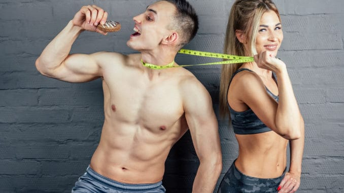 Beautiful blonde women in camouflage sports suit inflated and beautiful men with a measuring tape in the gym eating an orange and biscuits.