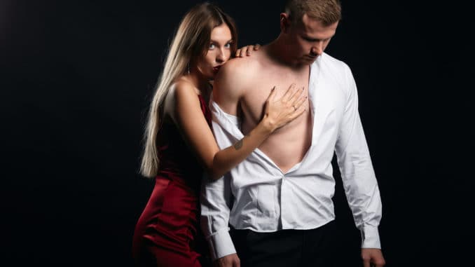 Passionate woman kissing her man`s shoulder