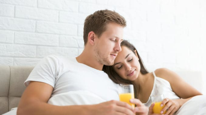 Happy young couple handsome man and beautiful woman lying in bed in bright bedroom in the morning drinking orange juice