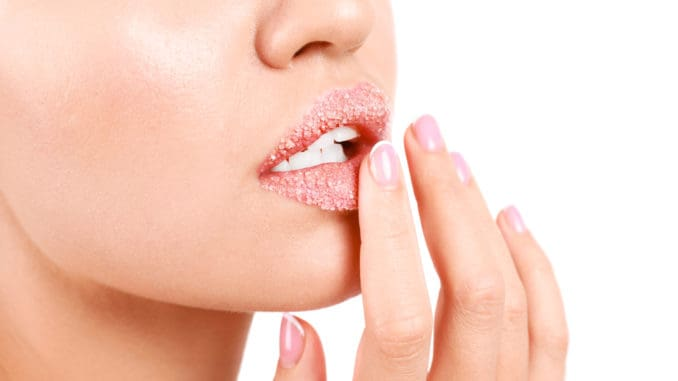 Young woman with sugar lips on white background, closeup