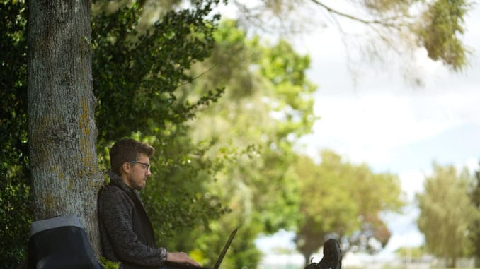 Man sitting under a tree, reposing and working on his computer.