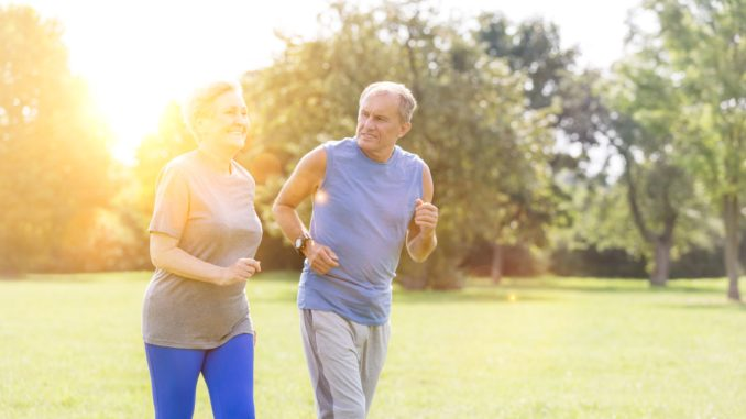Healthy senior couple jogging in park with yellow lens flare in background