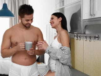 Young couple in white underwear drinking coffee at home