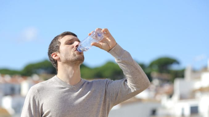 Casual adult man drinking bottled water standing in a rural town a sunny day
