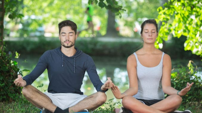 Couple doing yoga in a park