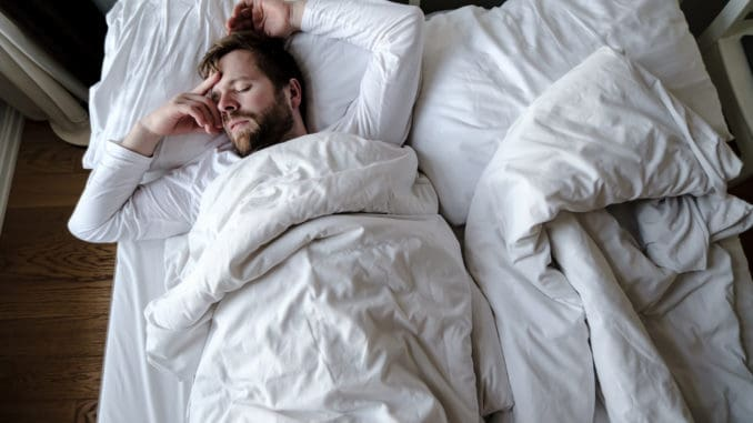 Bearded man sleeps restlessly in bed, he is alarmed and had a terrible nightmare.