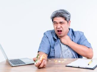 man having symptoms of food stuck in his throat Since he eats hamburgers