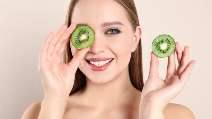 Young woman with cut kiwi on beige background. Vitamin rich food